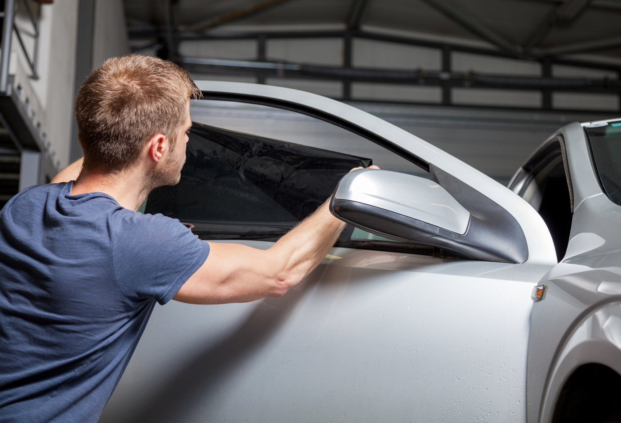 man applying window tinting